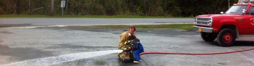 Child with firefighter and hose